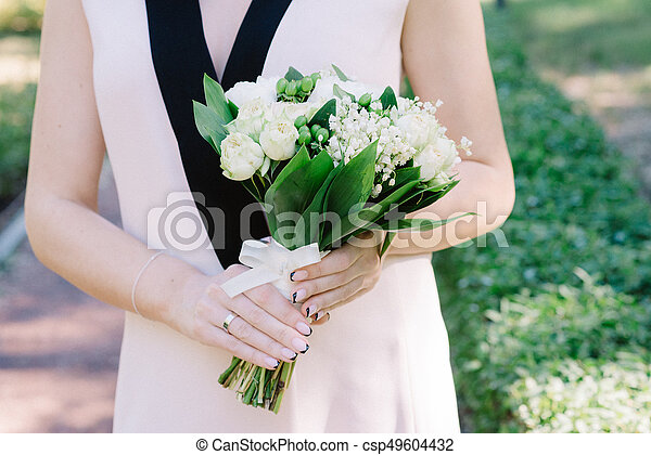 Elegant lily of the valley wedding bouquet in hands of the bride - csp49604432