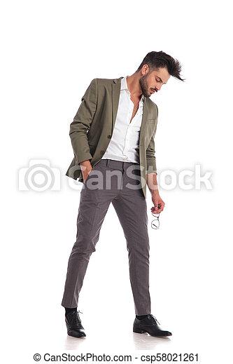 4c38532ec2 Elegant man posing while looking down to side. Elegant man with ...