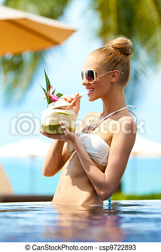 Elegant woman drinking a tropical cocktail - csp9722893