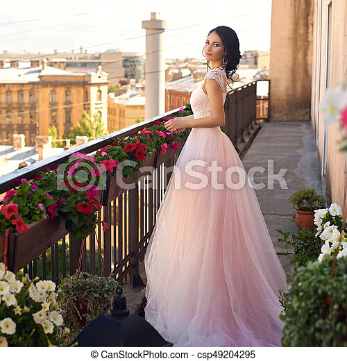 e721f0827ee Elegant woman in long fluffy pink dress. Tender outdoor full length ...