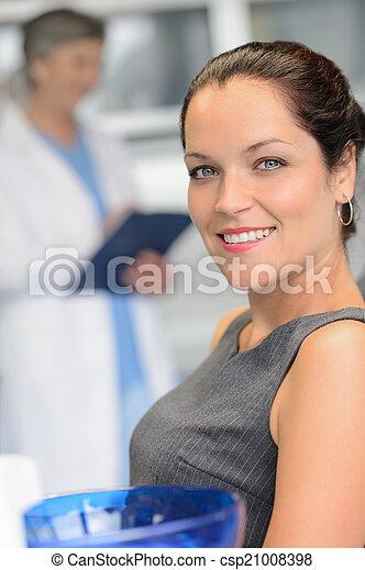Elegant woman patient at dentist surgery smiling - csp21008398