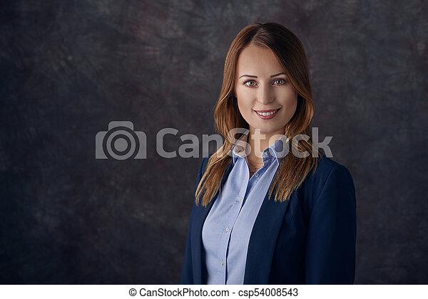 Elegant woman standing against dark