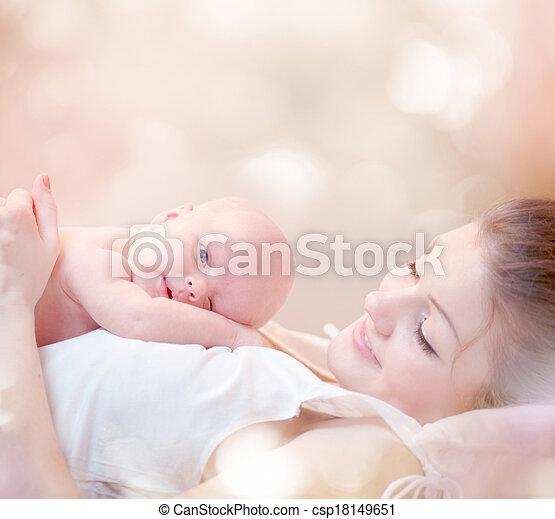 Madre feliz y su bebé recién nacido besándose y abrazándose - csp18149651