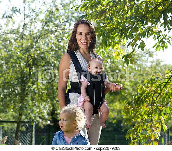 Madre feliz sonriendo con sus dos hijas pequeñas - csp22079283