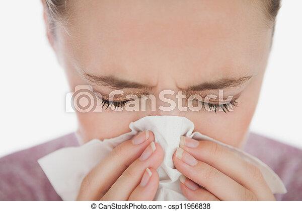 Una mujer con los ojos cerrados sonándose la nariz - csp11956838