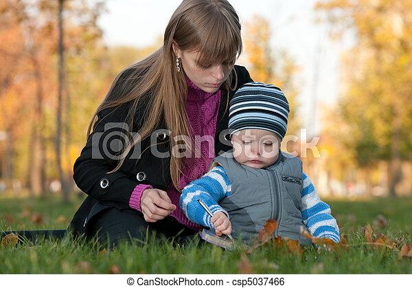 Mamá enseña a su hijo en el parque de otoño - csp5037466