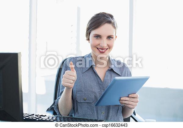 Bonita mujer de negocios mostrando los pulgares mientras sostenía su tableta - csp16632443