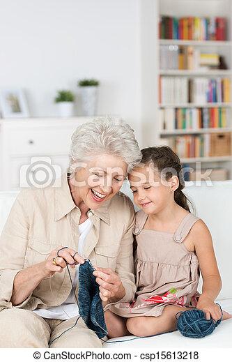 Señora mayor enseñando a su nieta a tejer - csp15613218