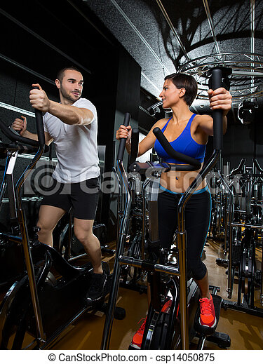 elliptical walker trainer man and woman at black gym - csp14050875