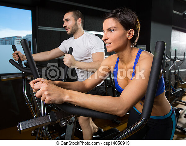 elliptical walker trainer man and woman at black gym - csp14050913
