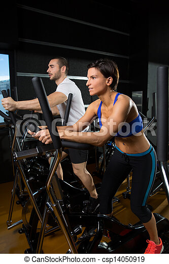 elliptical walker trainer man and woman at black gym - csp14050919
