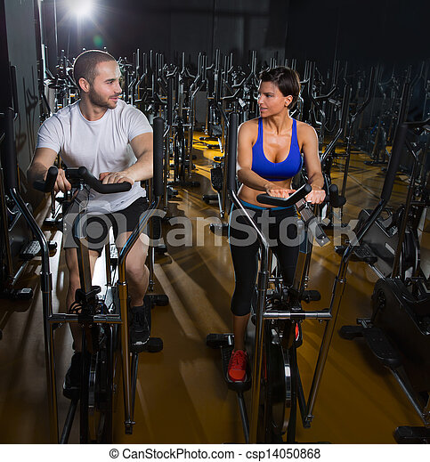 elliptical walker trainer man and woman at black gym - csp14050868
