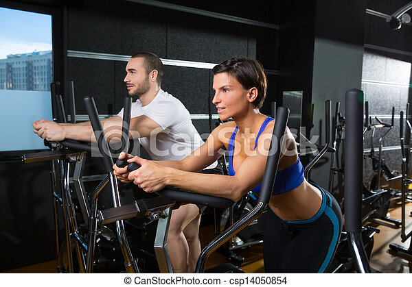 elliptical walker trainer man and woman at black gym - csp14050854