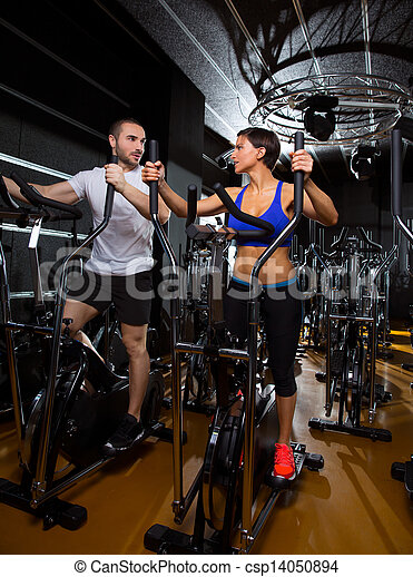 elliptical walker trainer man and woman at black gym - csp14050894