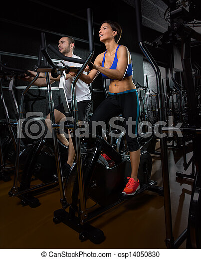 elliptical walker trainer man and woman at black gym - csp14050830