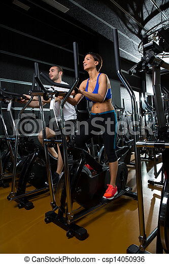 elliptical walker trainer man and woman at black gym - csp14050936