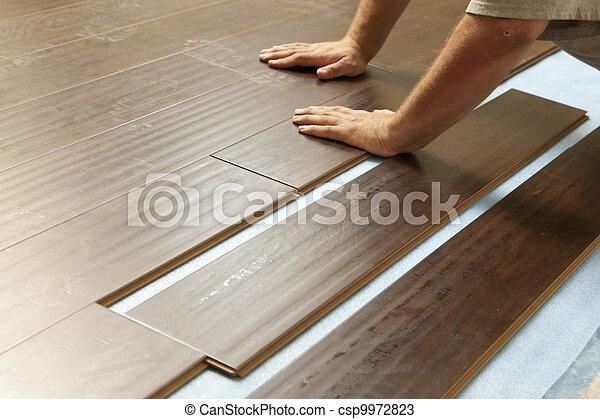 Hombre instalando nuevos suelos de madera laminado - csp9972823