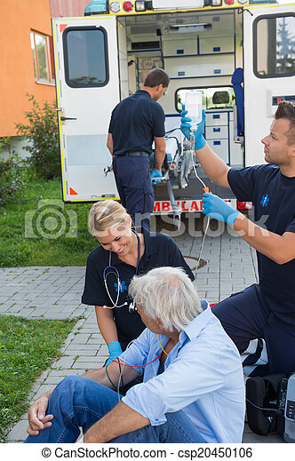 Emergency team treating injured patient on street - csp20450106