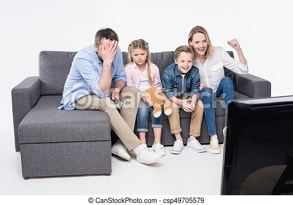Emotional Family Sitting On Sofa And Watching Tv Together   Csp49705579