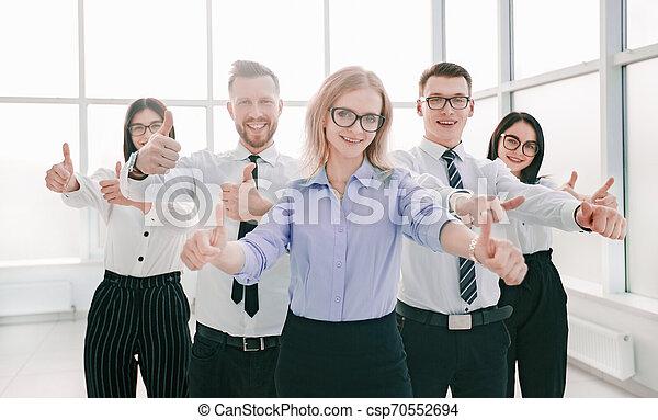 Feliz equipo de negocios mostrando sus pulgares hacia arriba - csp70552694
