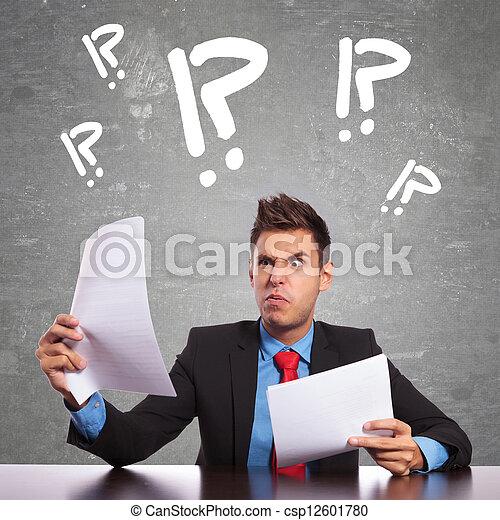 Hombre de negocios confundido leyendo documentos - csp12601780