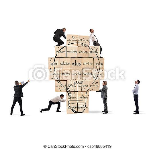 Construyendo una nueva idea creativa. Una persona de negocios construyó un gran muro de ladrillo con bombilla dibujada - csp46885419