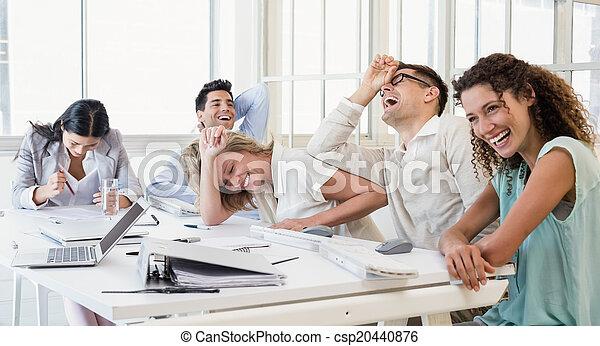 Equipo de negocios casual riendo durante la reunión - csp20440876