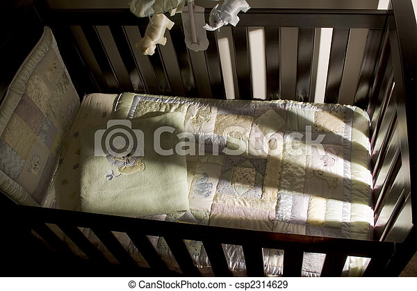 Empty baby cot with harsh side lighting coming through the slats - csp2314629