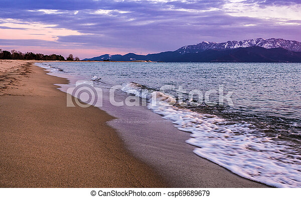 Empty beach in the evening - waves crashing on the sand - csp69689679