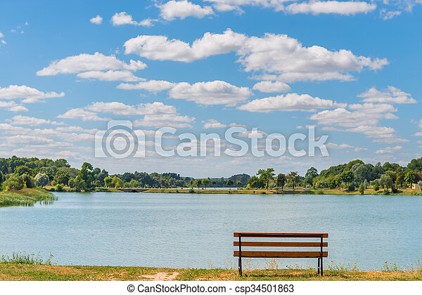 empty bench by the lake on a sunny day - csp34501863