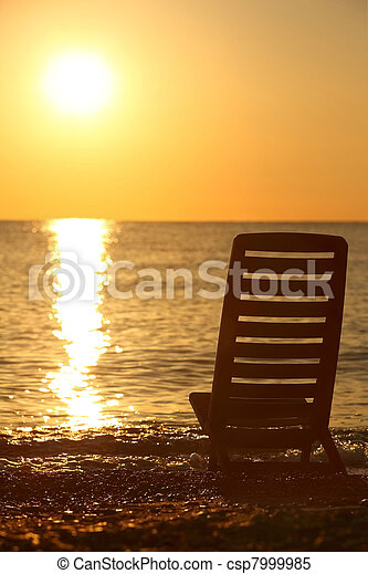 Empty chair stands sideways on  sea-shore in the evening during sunset - csp7999985