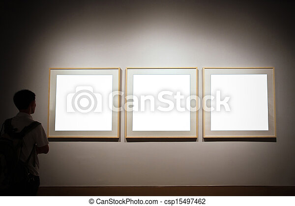 Empty exhibition frames and person looking . Walls in museum with ...