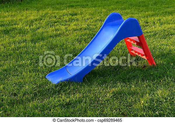 Empty green slide on grass in park - csp69289465