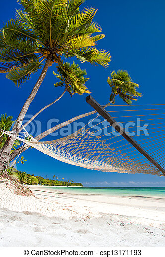 Empty hammock under palm trees and details of sand - csp13171193