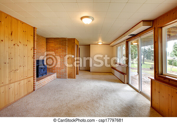 Empty living room with wood panel walls and cast iron pictures