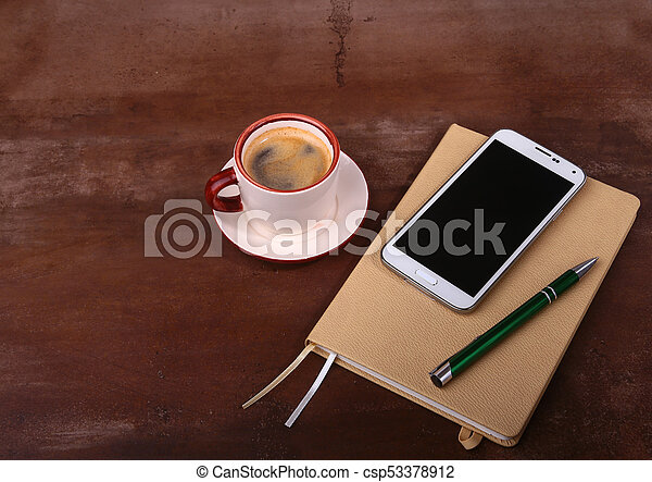 Empty notebook and ball pen with a cup of coffee, phone of the office desk. Business concept - csp53378912