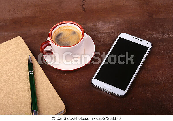 Empty notebook and ball pen with a cup of coffee, phone of the office desk. Business concept - csp57283370