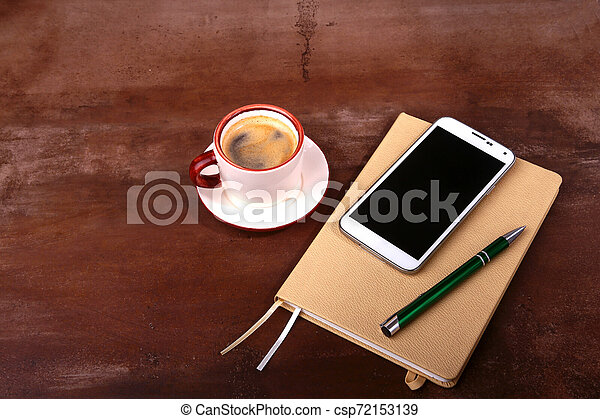 Empty notebook and ball pen with a cup of coffee, phone of the office desk. Business concept - csp72153139