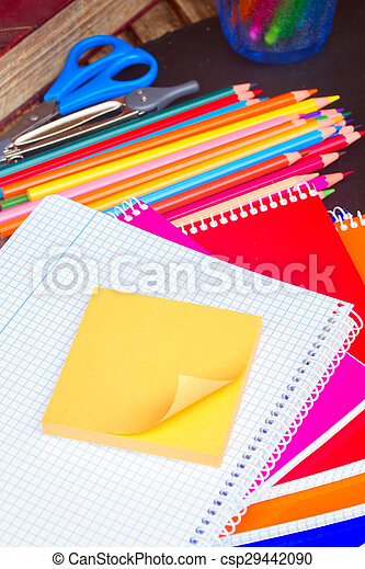 Empty notebook and set of colorful pencils on black board - csp29442090