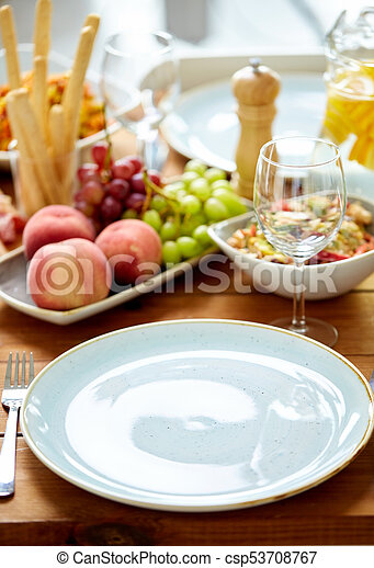 empty plate and wine glass on table with food - csp53708767