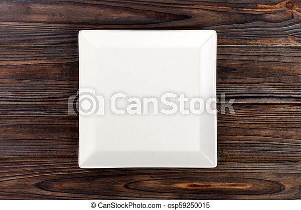 Empty square White Plate on Wooden Table Top View