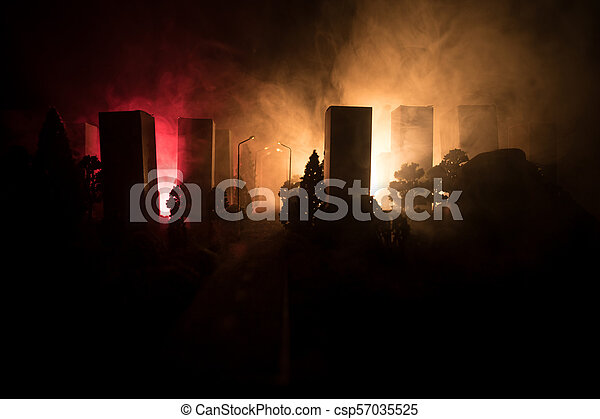 Empty street of burnt up city, flames on the ground and blasts with smoke in the distance. Apocalyptic view of city downtown as disaster film poster concept. Night scene. - csp57035525