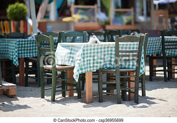Empty Tables and Chairs on Sunny Restaurant Patio - csp36955699