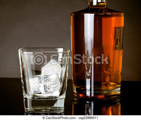 empty whiskey glass with ice near bottle on black background - csp23986411