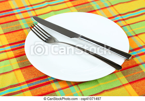 Empty white plate on colorful napkin - csp41071497