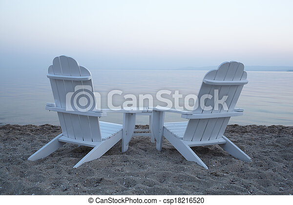 Empty wooden deck chairs on a beach - csp18216520