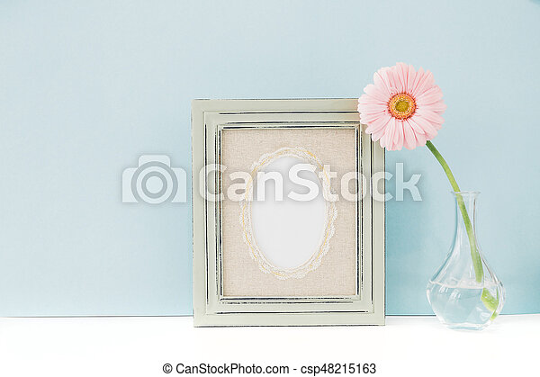 Empty Wooden Frame And Flowers In Vase On Table On Blue Background