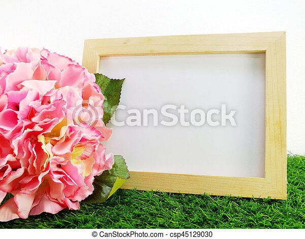 empty wooden frame with flower on green background - csp45129030
