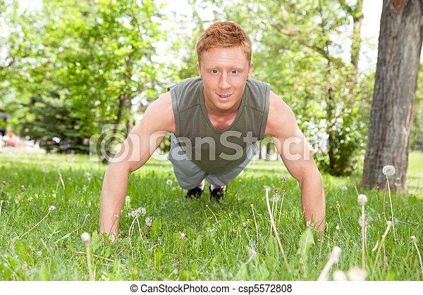 Un hombre empujando en el parque - csp5572808