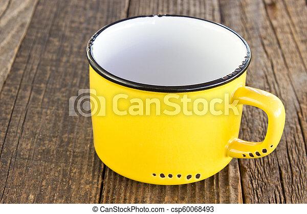 Enamel yellow mug on wooden background - csp60068493